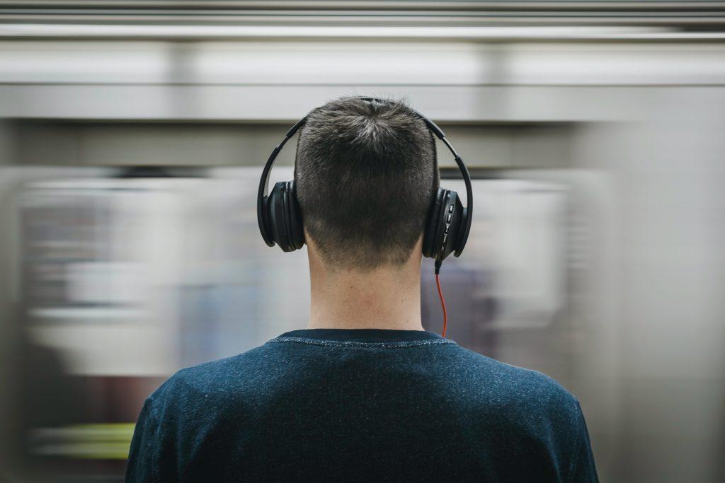 Uomo ascolta musica in cuffie. Nell'articolo di parla di audio 8D.